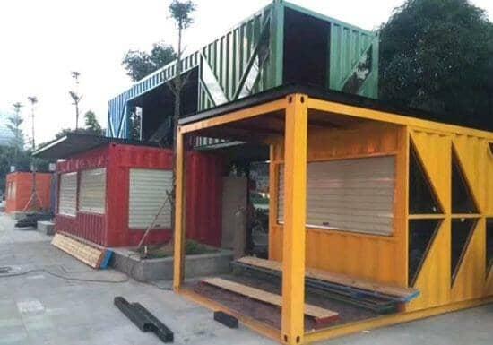 绿色箱房骑在红色与黄色箱式活动房的头上,真是一桩美丽的的风景线呀
